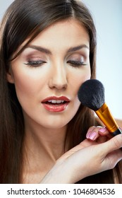 Beautiful woman using brush for make up applying. Isolated portrait.