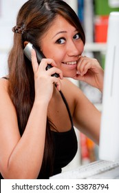 A beautiful woman using the computer whilst talking to her friend on the phone