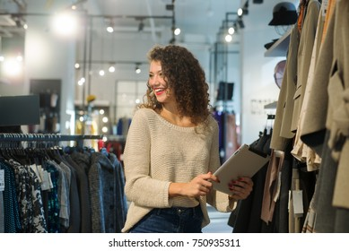 Schöne Frau, die eine digitale Tablette im Laden benutzt.