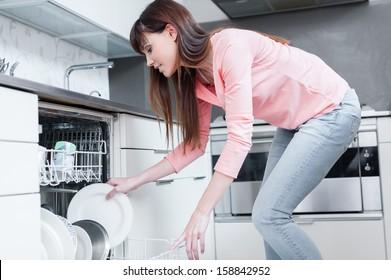 A beautiful woman using a dishwasher in a modern kitchen. domestic appliance