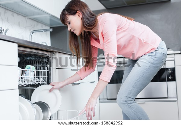 A beautiful woman using a dishwasher in a modern kitchen. domestic appliance