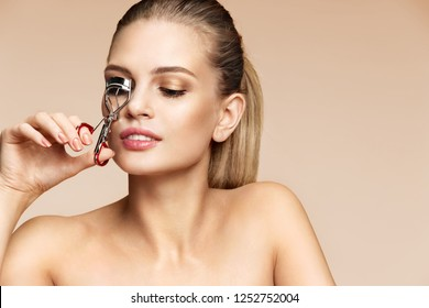 Beautiful woman using eyelash curler on long eyelashes. Photo of attractive woman with perfect makeup on beige background. Beauty concept