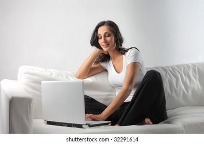 beautiful woman using laptop on a sofa
