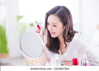 Beautiful Woman using mascara brush and look mirror at home