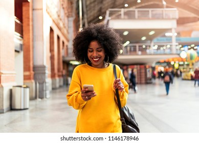 Beautiful woman using mobile in the train station. Communication concept