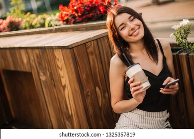 Beautiful woman using phone and drink coffee on the streets.