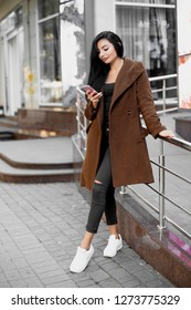 Beautiful woman using the phone on the street.