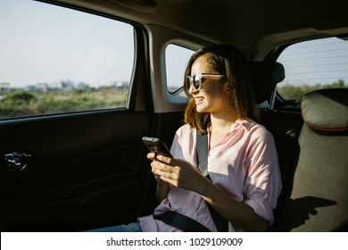 Beautiful woman is using a smart phone and smiling while sitting on back seat in the car