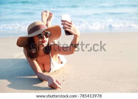 beautiful woman using smart phone while on holiday vacation doing self portrait with happy face and kissing to camera on the beach (this image for relaxation with technology background concept)