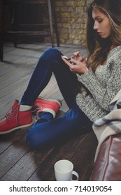 Beautiful woman using smartphone holding at hands wearing warm clothing at loft apartment. Relax time during cold weather