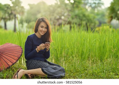 Beautiful Woman are using smartphone on the field,thai traditional culture,Thailand