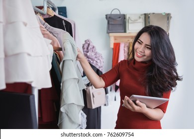 Beautiful woman using tablet while working in the store