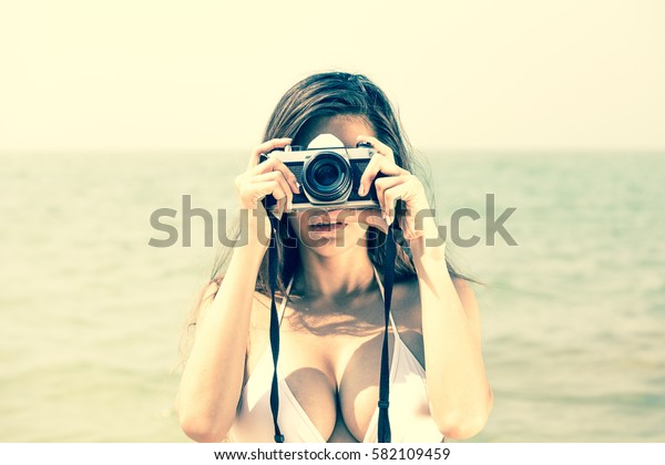 Beautiful woman using vintage camera at the summer sand beach. Outdoor summer portrait, vintage color style.