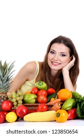 Beautiful woman with vegetables and fruits on table isolated on white