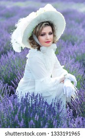 beautiful woman in victorian vintage style outfit and hat sitting on lavender field