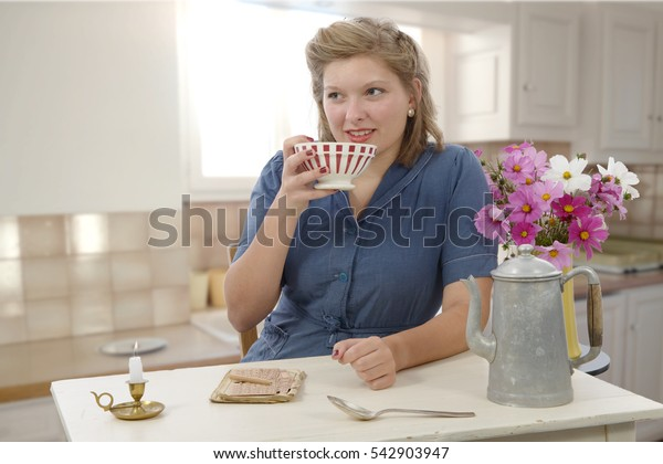 beautiful woman with vintage clothes drink a coffee in the kitchen