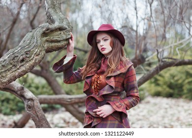 Beautiful woman in a vintage clothing and elegant hat in a misterious forest