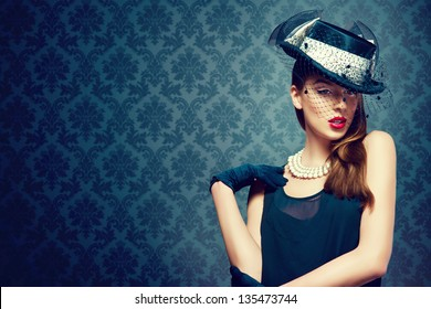 Beautiful woman in a vintage hat over a fashion background