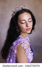 beautiful woman in violet dress and crown