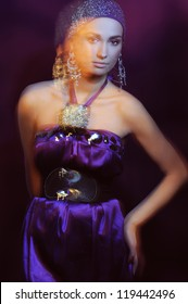 Beautiful woman in violet evening dress and beautiful jewelry in motion blur light