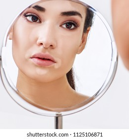 Beautiful woman with vitiligo looking on her reflection in the mirror. Over white background.