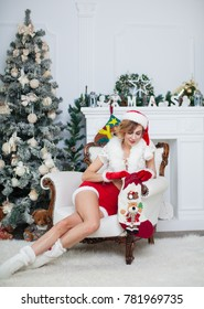 Beautiful woman is waiting for a new year sitting near the Christmas tree