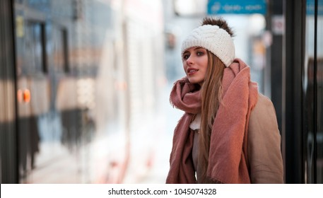 Beautiful woman waiting for tram at city bus stop