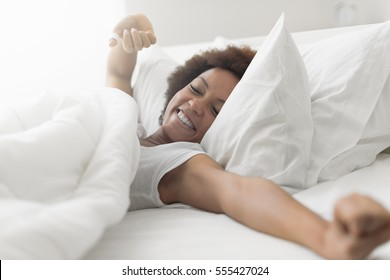 Beautiful woman waking up in her bed, she is smiling and stretching