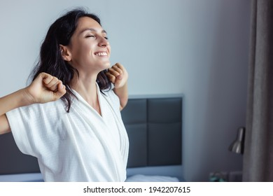 Beautiful woman waking up on her bed at bedroom Young Female stretching and smiling overjoyed Beauty Lady wake up meet good weekend early morning Young lady feel optimistic at home with smile face