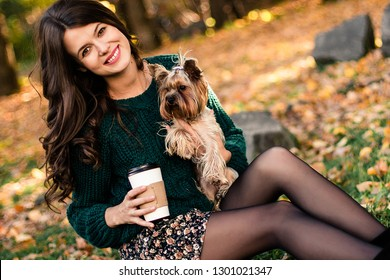 Beautiful woman walk with dog and drink coffee in the park.