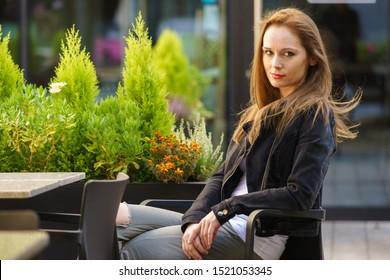 Beautiful woman walking around modern city wearing black jeans jacket. Female fashion model during spring weather, having long brown hair wind tousled.