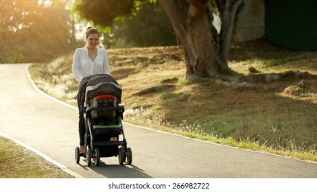 Beautiful woman walking down a lane in park with her little daughter and pushing pushchair, talking to her baby and smiling. Full length view at sunset