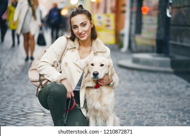 beautiful woman walking her dog in the city during the day