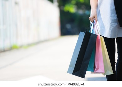Beautiful woman walking and holding many shopping bags with copy space