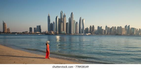 Beautiful woman is walking on the beach and looking to Dubai Marina Skyline