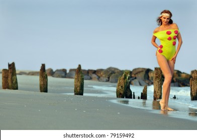 Beautiful woman walking on the beach in lime color designer's swimsuit