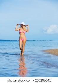 Beautiful woman walking on tropical beach
