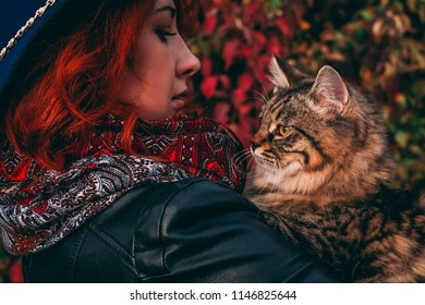 Beautiful woman is walking in the park in cloudy weather in the fall.  Female in a leather jacket, scarf, blue hat, with a kitty in her hands at fall walks