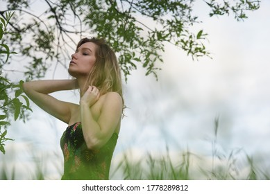 A beautiful woman walks in a field in the tall wet grass after the rain.