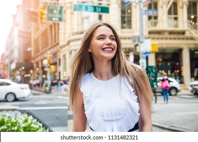 A beautiful woman walks on city street to the office at the morning and enjoy her day