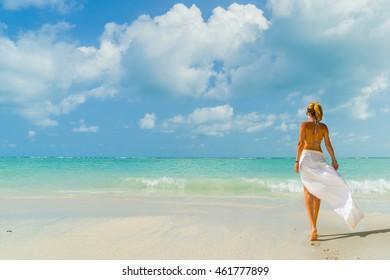 Beautiful woman walks on the tropical beach
