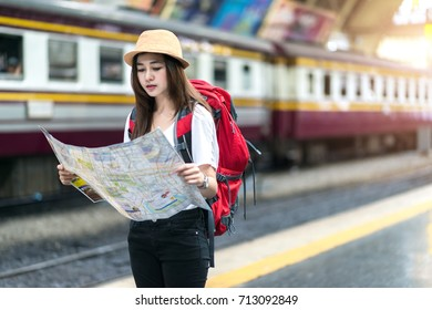 Beautiful woman wanderer tourist look searching direction on location map while traveling at train station, Happy female tourist searching road to hotel on map foreign city during vacation