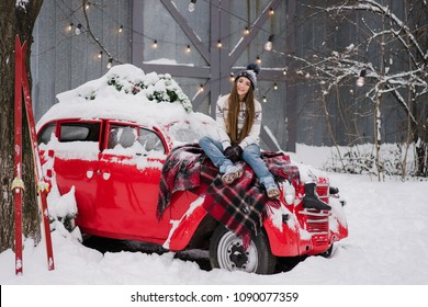 Beautiful woman in warm cozy clothes sitting on red vintage car covered with snow. Cold happy winter day. Holidays, christmas, winter, love, beauty concept