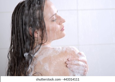 Beautiful woman washing her body shower gel