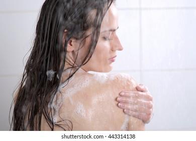 Beautiful woman washing her body shower gel