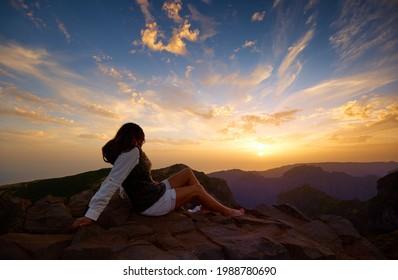Beautiful woman watching atmospheric sunset over mountains of Madeira Island. Colorful blue sky background, orange clouds, dark steep mountains. Pico do Arieiro, Madeira Island, Portugal.