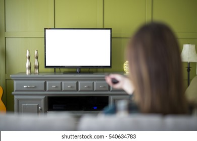 A Beautiful woman watching TV sitting on couch at home