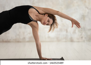 Beautiful woman wear black sportswear performs Bending Side Plank Vasisthasana yoga asana, powerful arm and legs strengthener benefits improve concentration, healthy physical mental lifestyle concept