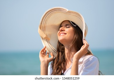 Beautiful woman wear sun hat relaxing on a beach. Blue sky, Summer, Vacation, Holiday.