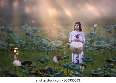 Beautiful woman wearing ao dai dress in lotus garden at sunset.
